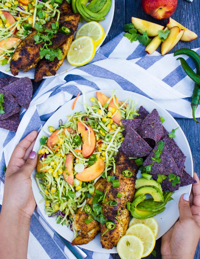two hands holding a plate of fish taco recipe with taco slaw and chips