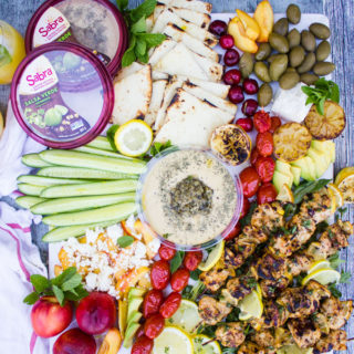 Lemon chicken and hummus platter showing hummus tube surrounded by lemon chicken, grilled lemon, olives, grilled tomatoes, charred bread, cucumbers, peach salad and feta cheese