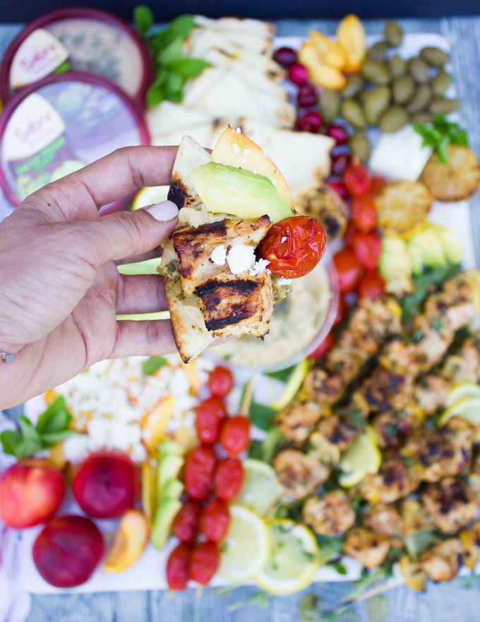 A hand holding a piece of bread topped with sabra hummus, lemon chicken and grilled tomatoes, sliced avocados and feta cheese