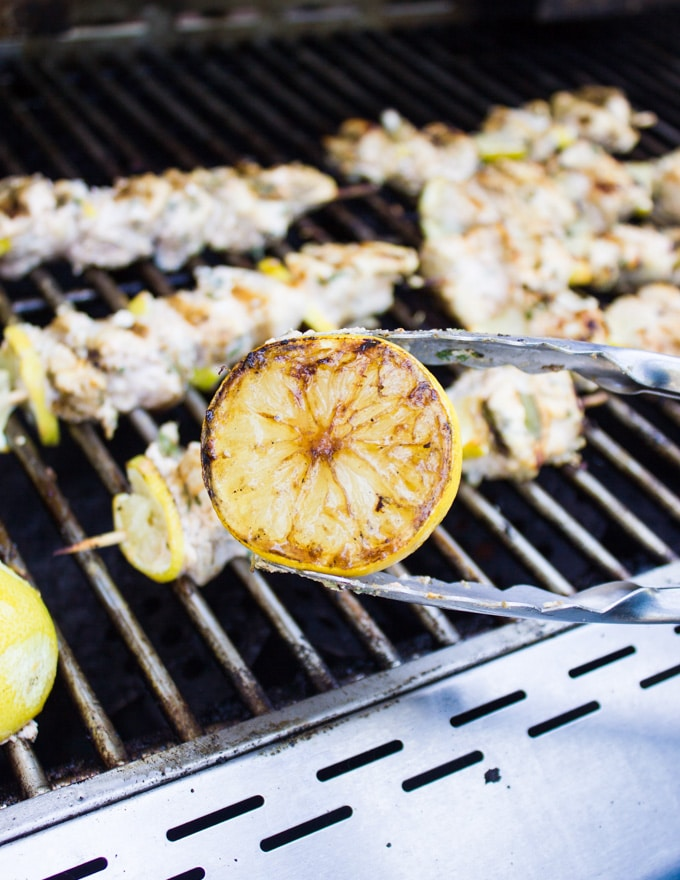 A tong showing a lemon grilled on the BBQ for the lemon chicken with the lemon chicken grilling behind