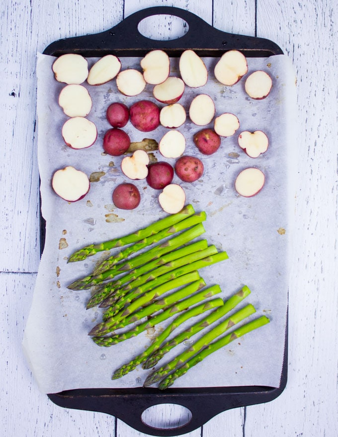 A pan with asparagus and potatoes ready for the grill