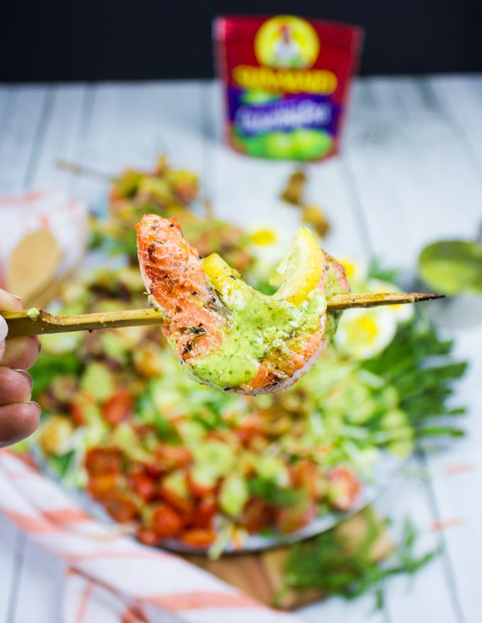A hand holding the grilled salmon skewer right over a platter of salmon salad and drizzled with a dollop of dill dressing