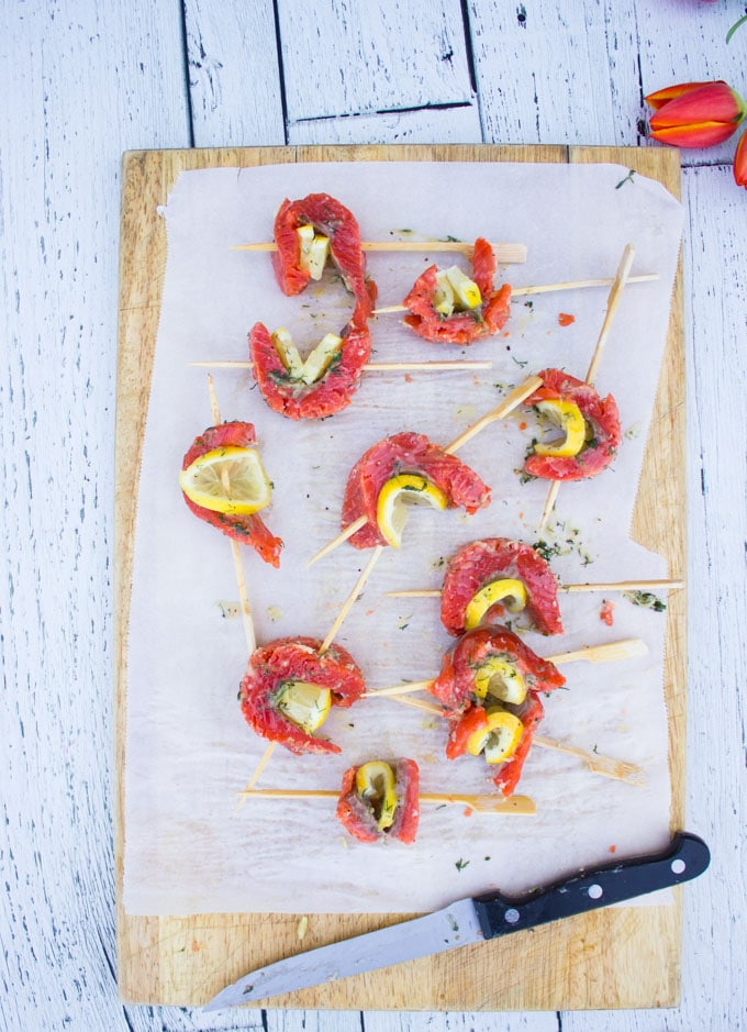 a set of salmon skewered with lemon slices and ready to grill for the salmon salad