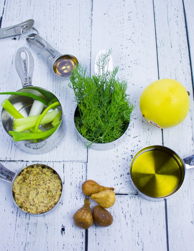 Sweet Dill Dressing ingredients showing olive oil in a cup, some figs, a lemon, some dill in a cup, scallions in a cup and a spoon of honey