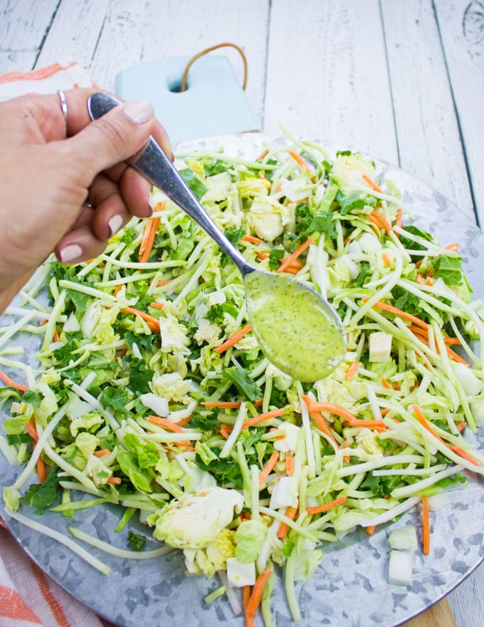 A hand drizzling some sweet dill dressing over the slaw mix