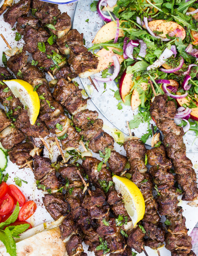 Close up of the grilled lamb skewers with lemon wedges