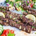Side view of one grilled lamb skewer