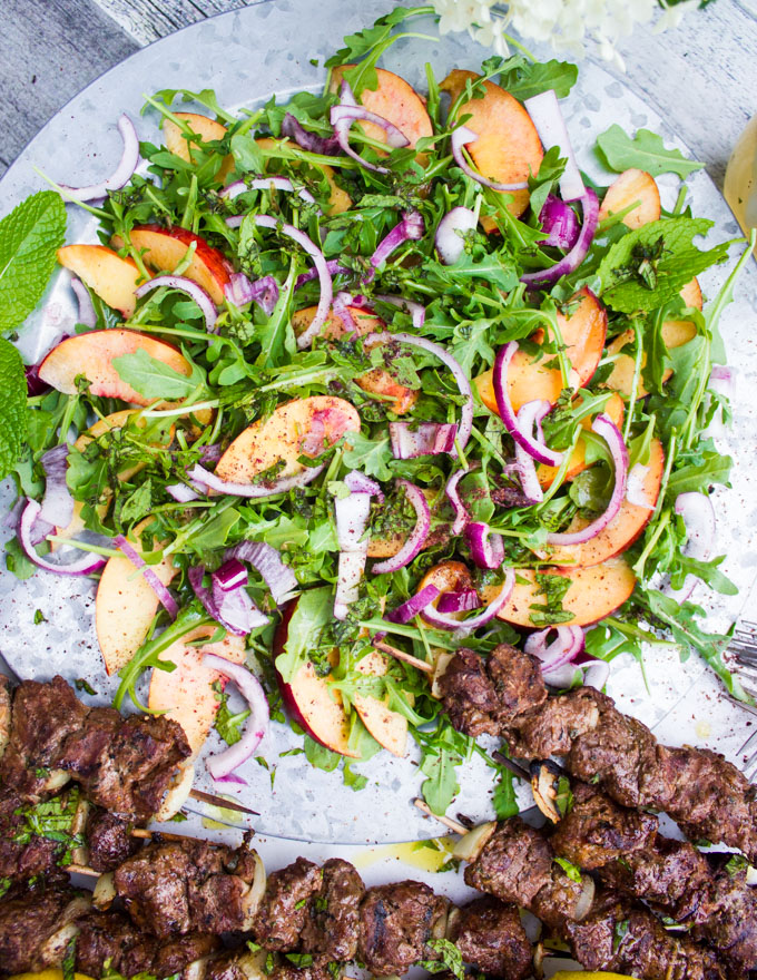 A plate of the peach salad surrounded by two grilled lamb skewers