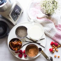 Ingredients for chia seed pudding: chia seeds, dates, milk, vanilla and cocoa powder and a blender