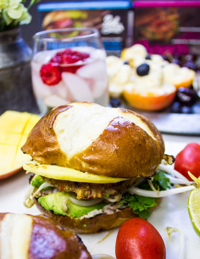 A full veggie burger close up showing the pretzel buns, avocados, onions, cilantro and Asian slaw next to it
