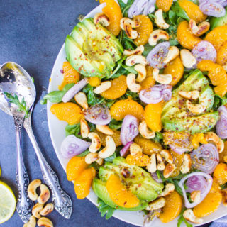 A half plate showing details of the Avocado Salad with oranges, citrus dressing, two spoons and some cashews