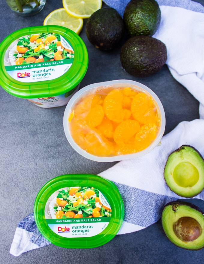 An open container showing the mandarin orange segments and surrounded by avocados to make the avocado salad