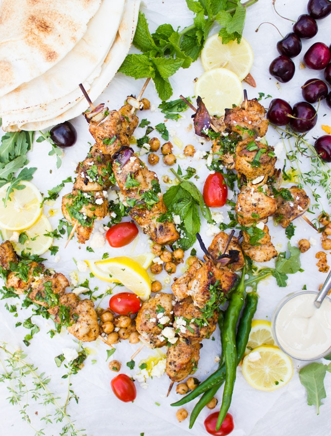 Grilled Chicken Skewers with spicy chickpeas, lemon wedges, feta crumbles, pita bread and tahini sauce.