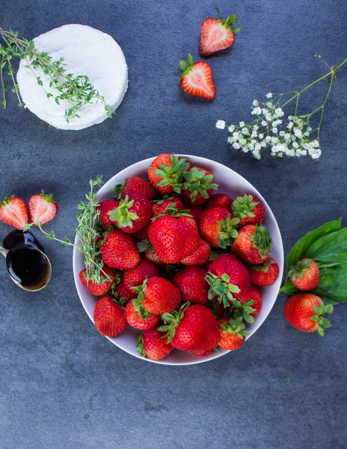 A bowl of Strawberries surrounded by a round of brie cheese, a spoonful of balsamic vinegar, fresh basil leaves and white flowers