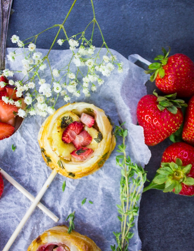 A savory hand pie on a lollipop stick with strawberries surrounded by fresh strawberries, fresh thyme and white flowers