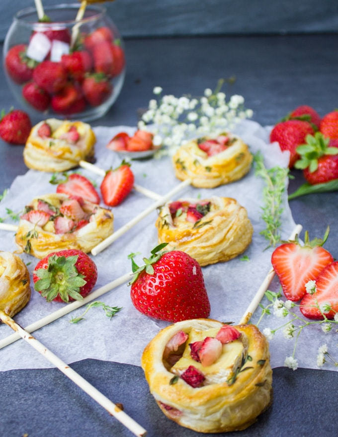 The strawberry savory hand pies piled together on a paper durrounded by fresh tsrawberries and a bowl of strawberries