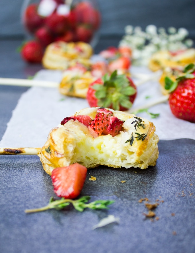 A baked hand pie on the surface bitten out to show the flakey texture, creamy brie cheese and sweet strawberries on top