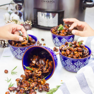 two hands grabbing the spiced mixed nuts from different bowls