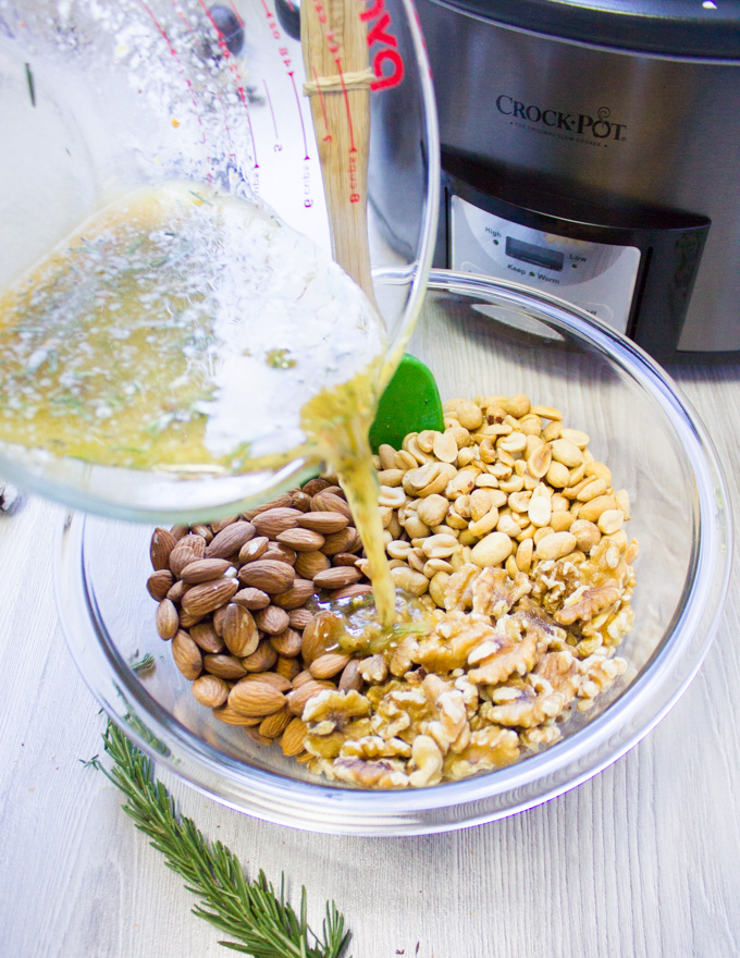The butter and spice ingredients being poured over a bowl of mixed nuts