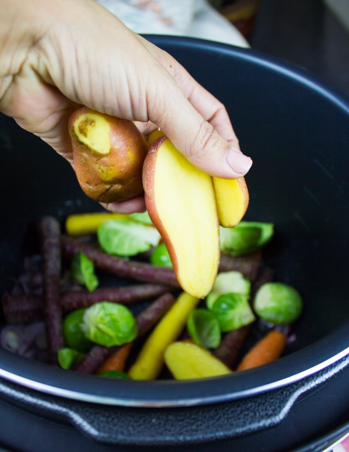 A hand adding in the veggies to the Crock-Pot over sauteed onions