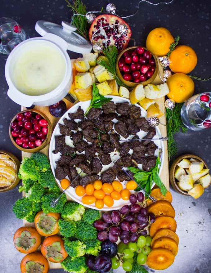 board of cheese fondue with cheese fondue dippers incuding lamb chunks, fruits and veggies and croutons.