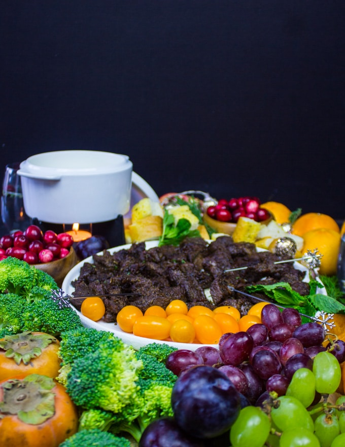 A side view of the cheese fondue platter with the pot of cheese fondue and all the veggies and fruits around it.
