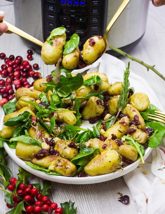 two spoons serving some potato salad recipe with spinach and cranberries and nuts.