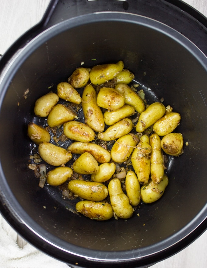 Potatoes getting golden with butter on the sear function in the Crock-Pot