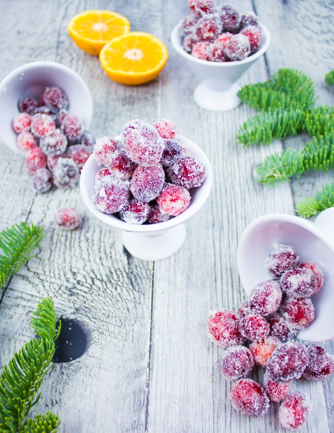 three bowls of sugared cranberries with clementines