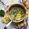 A large pot of soup with a ladle in the middle. Lemon slices are topped on the minestrone soup and surrounded by parsley and more lemons