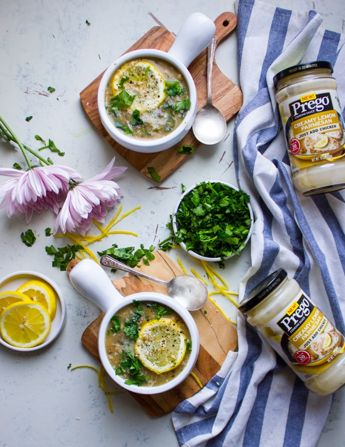 two bowls of minestrone soup surrounded by pink flowers, lemon slices, and jars of prego lemon sauce