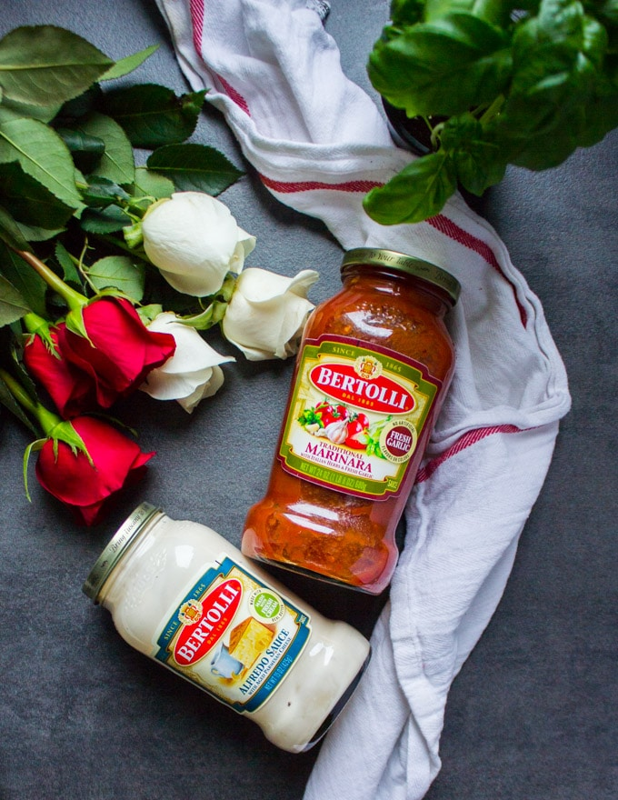 two jars of bertolli sauces next to a bunch of roses