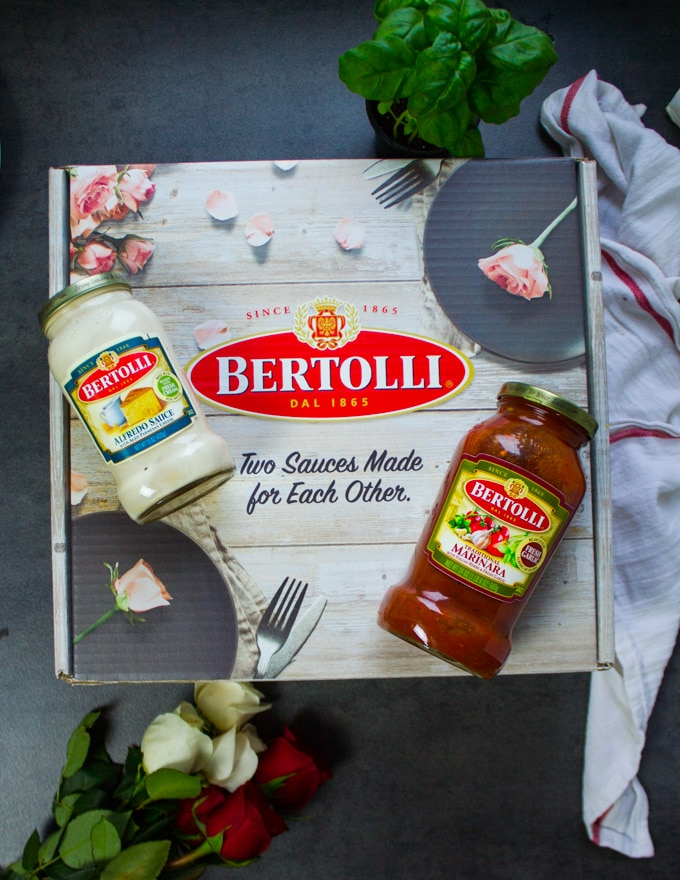 A box of Bertollli with two jars of sauces on top of it