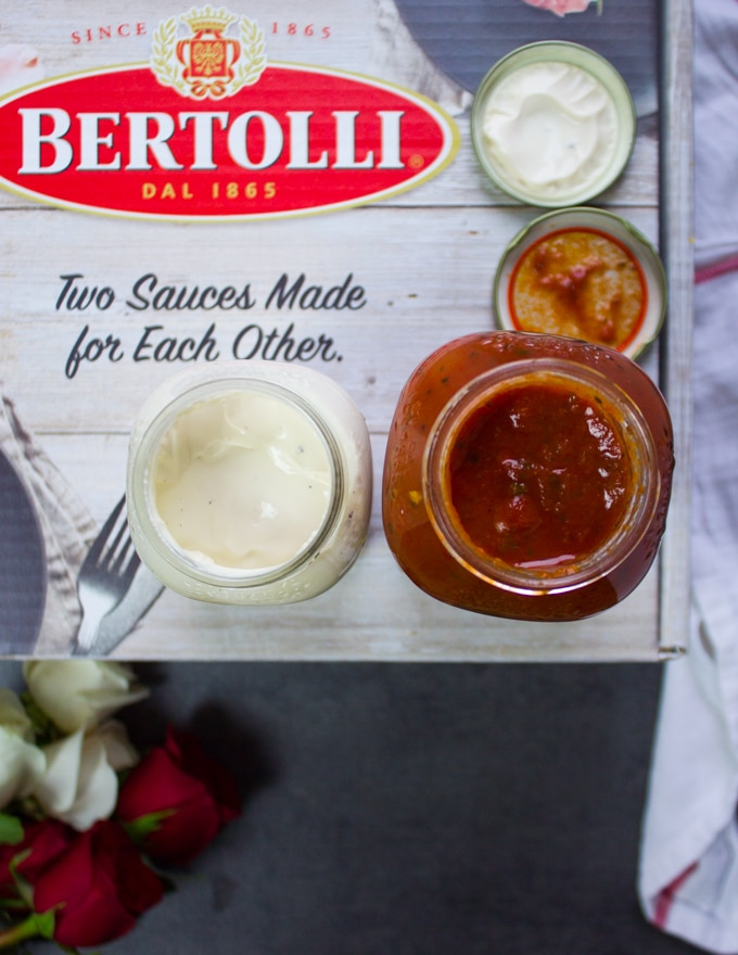 two jars of Bertolli sauces, one marinara sauce and one alfredo sauce opened up to show the inside