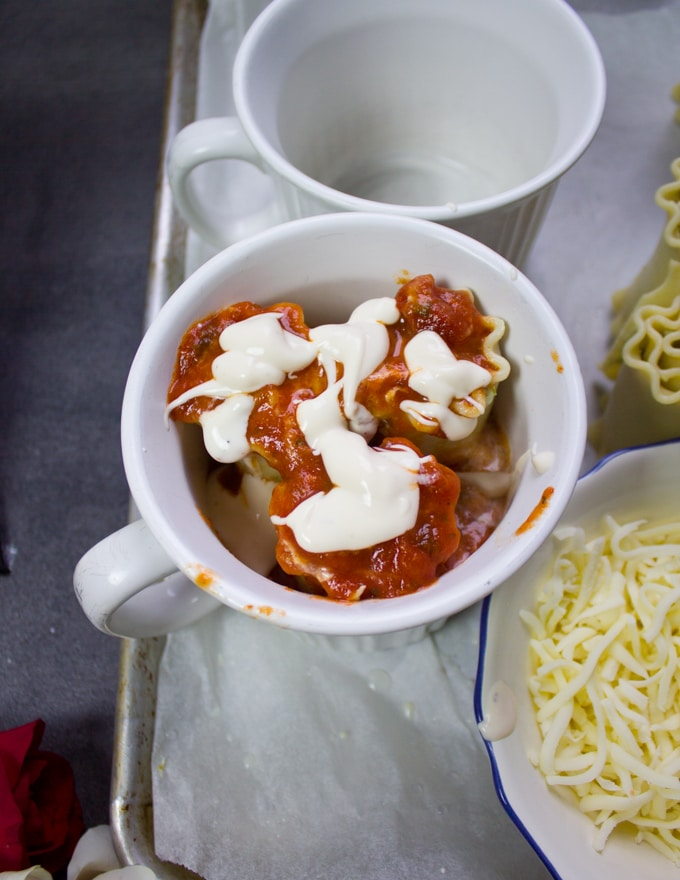 More marinara sauce and alfredo are put over the lasagna