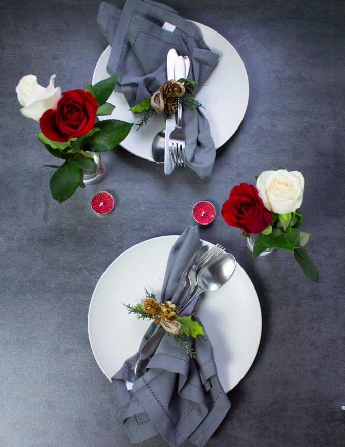 A table set up for two for valentine's day at home with plates, napkins or roses