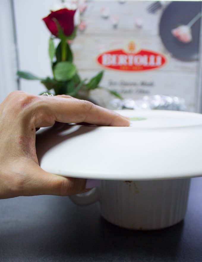 A hand holding a plate over the mug ready to flip