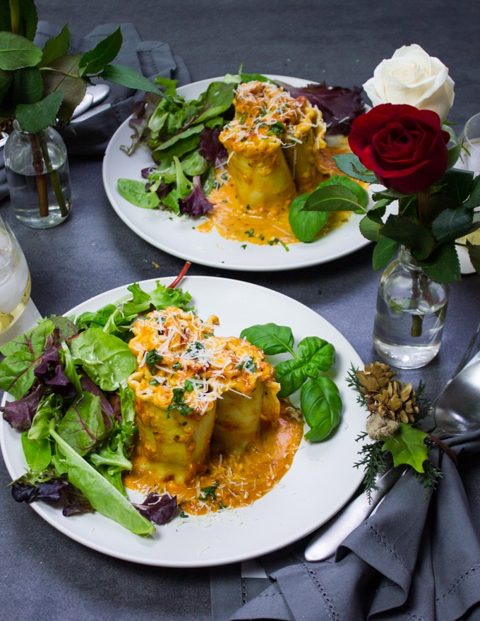 two plates with lasagna roll ups in rosa sauce on it. A red rose flower around that and a simple salad