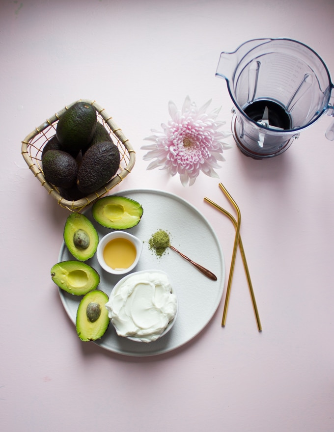 A plate with a cup fof yogurt, some avocados sliced in half, a little bit of honey, a teaspoon of matcha and a blender.f