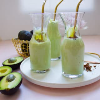 3 glasses of avocado smoothies with golden straws on a white plate