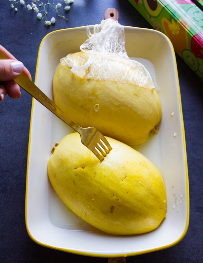 A fork piercing in a spaghetti squash half to make sure it's cooked through