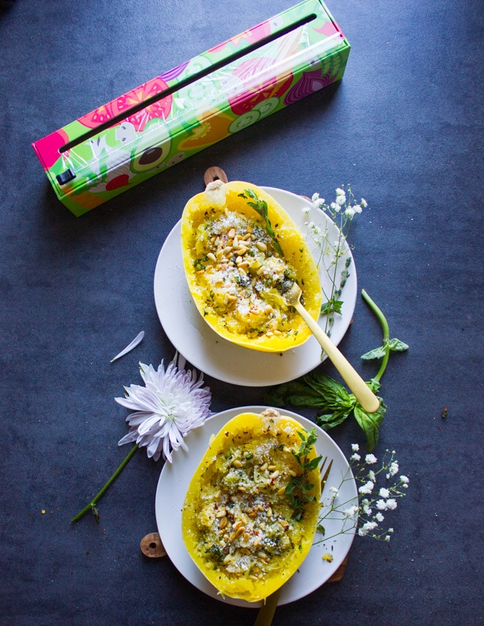 two spaghetti squash halves recipe loaded with parmesan, herbs and pine nuts on two plates and a flower in between