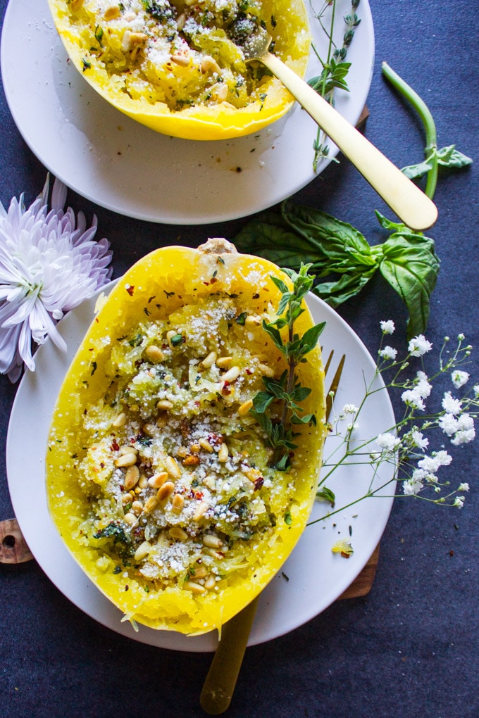 One cooked spaghetti squash recipe with parmesan, herbs, pine nuts and basil on a plate surrounded by a basil leaf and a flower.
