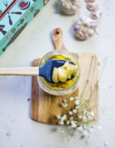 A spatula scoping some roasted garlic form the jar