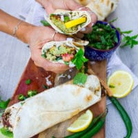 A hand holding a sandwich cut in half over a board of falafel sandwiches, lemon slices and green chillies