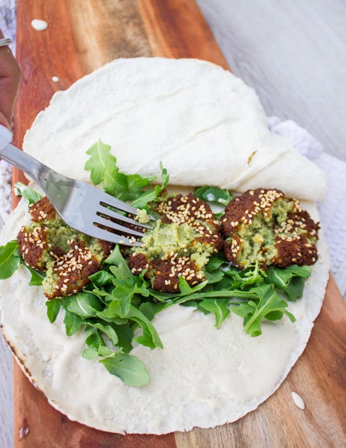 A fork mashing the falafel inside the sandwich before piling the topping
