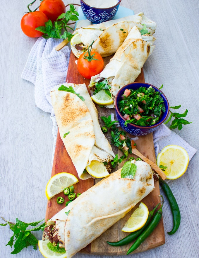 A set of four falafel sandwiches over a wooden board surrounded by lemon juice and tabouleh salad