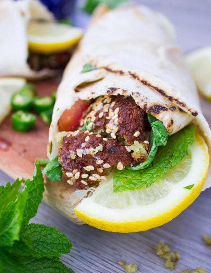 A finished falafel wrap close up showing the flafel, fresh mint and lemon slices.
