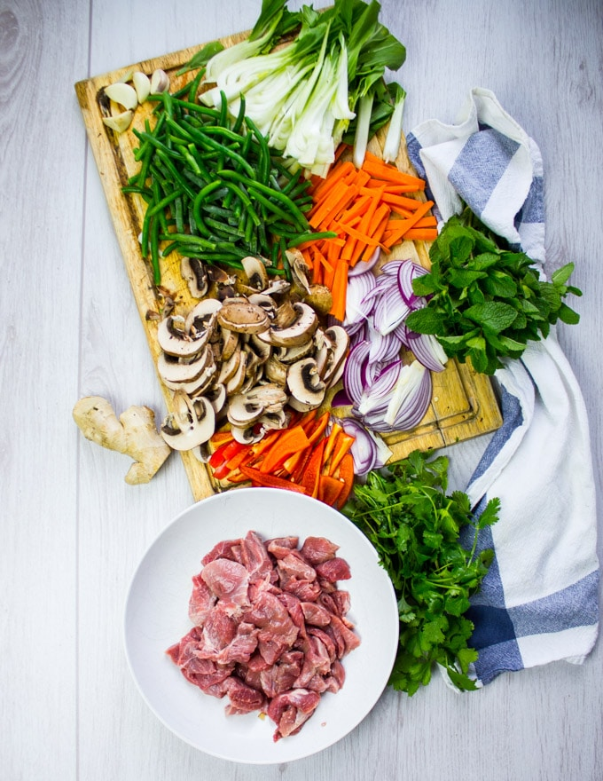 A bowl of thinly sliced lamb and a board with all the veggies ready to be used for the stir fry