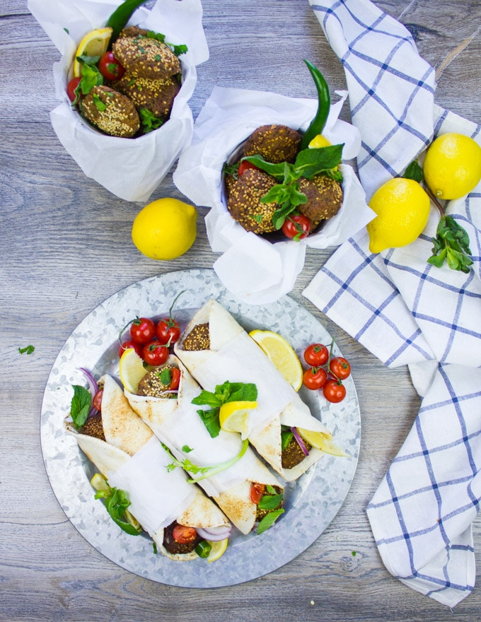 A plate of falafel wraps next to buckets of freshly fried falafel surrounded by mint, tomatoes and lemons